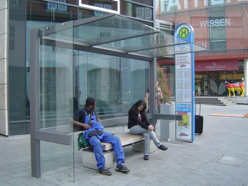 Zwei Personen sitzen in  der Wartehalle Meilenstein